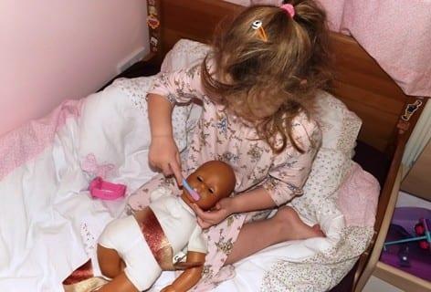 Erin cleans her dolls teeth before getting dressed.